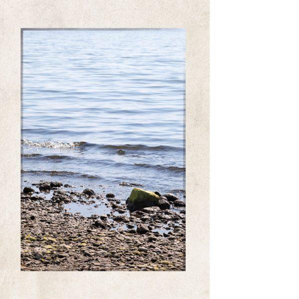 Kannessa kivinen ranta, johon laineet liplattavat.