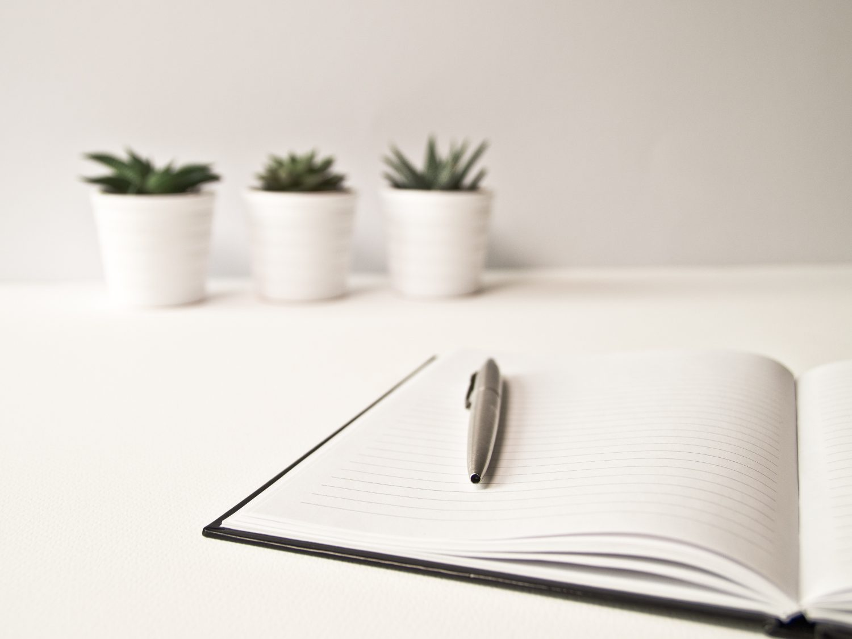 Muistikirja, jonka päällä kynä ja taustalla viherkasveja.